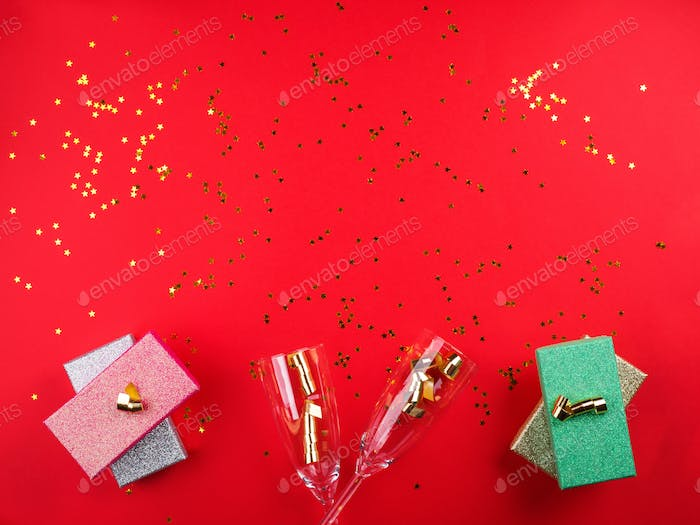 Champagne flutes and presents on red. Confetti