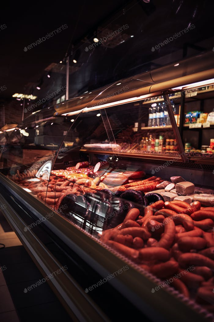 Fresh ham and sausages in meat shop's counter