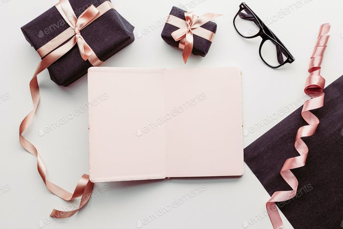 Notebook, eye glasses and gift box on white background.