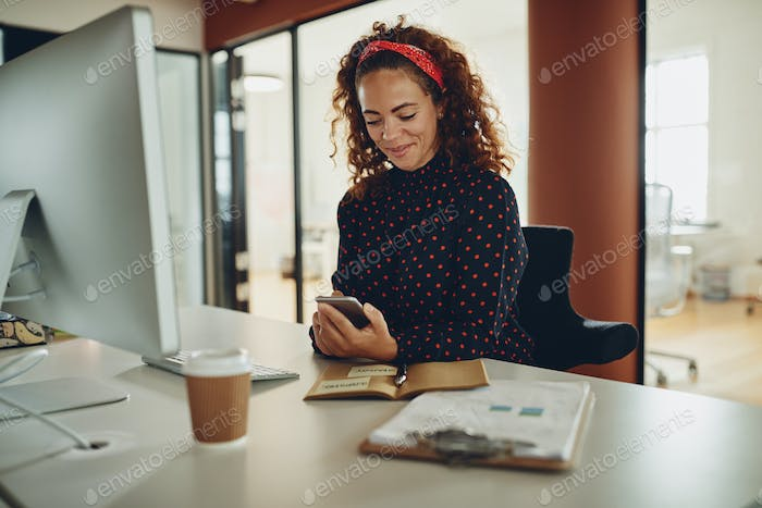 Smiling businesswoman reading a text message at her office desk