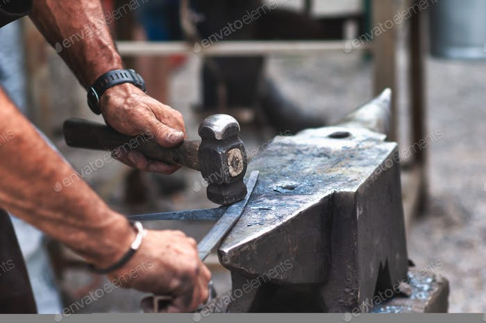 An artisan blacksmith knocks