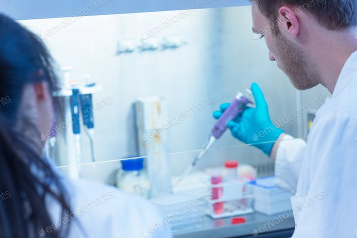 Science student using pipette in the lab at the university