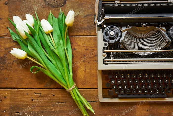 Bouquet of white tulips and typewriter on wooden backgound top v