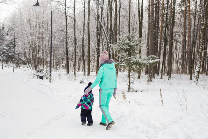 happy mother and baby girl on the walk in winter snowy forest