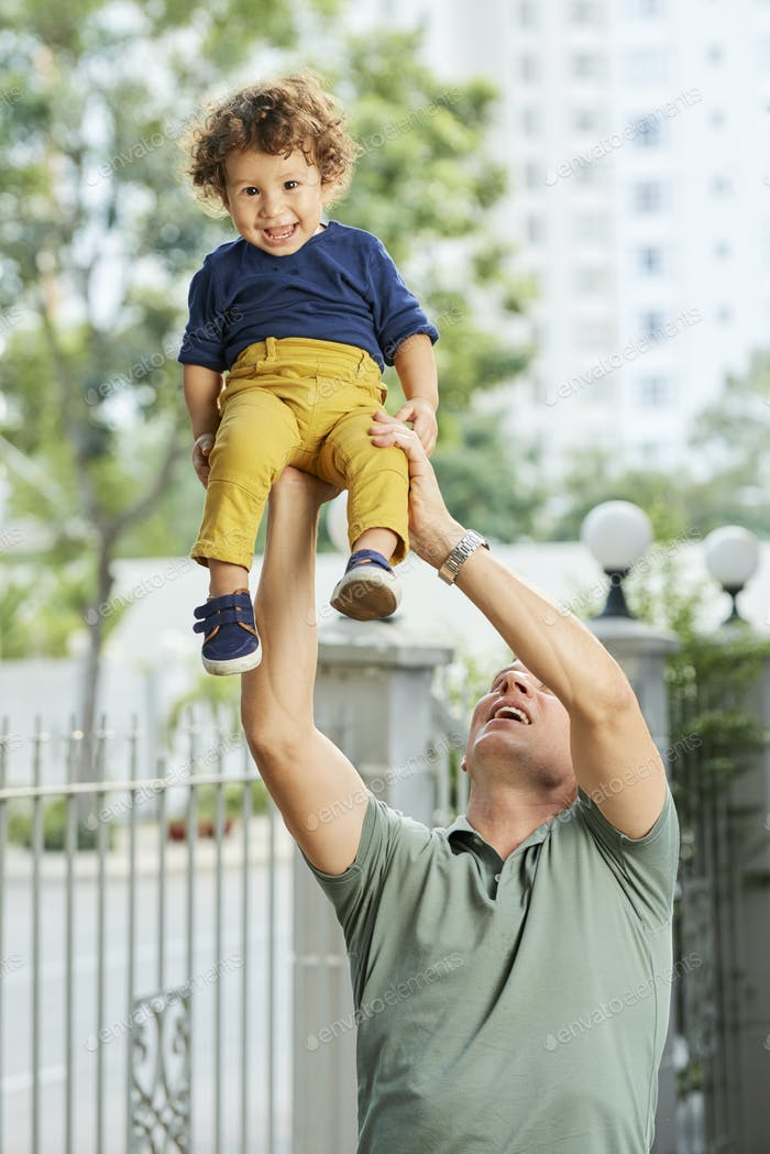 Padre levantando a un niño pequeño