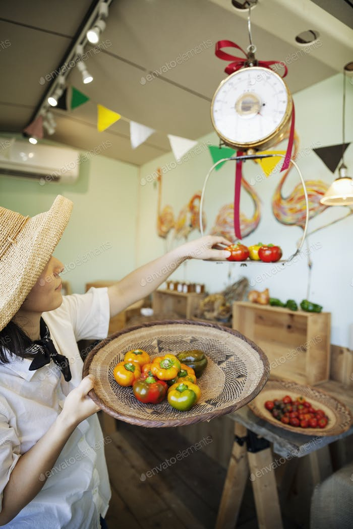 Japanese woman wearing hat working in a farm shop, weighing fresh vegetables.