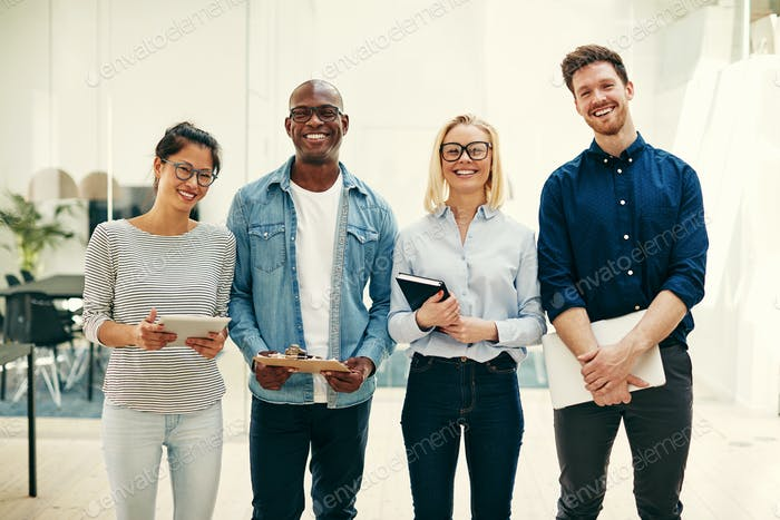 Group of diverse businesspeople laughing together in a modern office