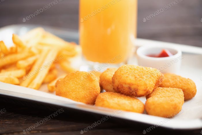Close up chicken nuggets and fries with sauce and juice on plate