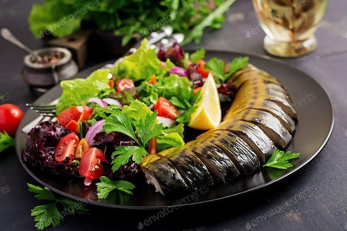 Smoked mackerel and fresh salad on dark background.