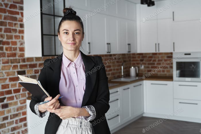 Portrait of smiling real estate agent in new apartment
