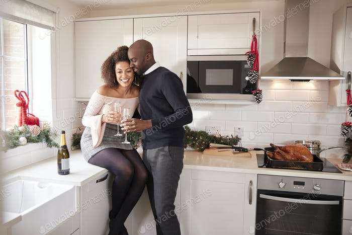 Young mixed race couple drinking champagne embrace in their kitchen while preparing Christmas dinner
