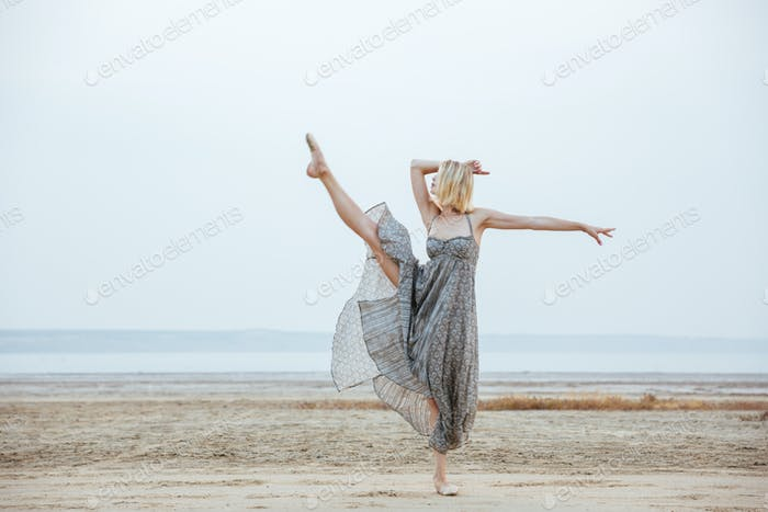 Graceful young woman dancer dancing on the beach