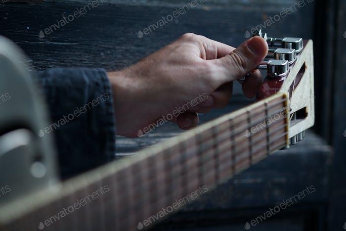 Abstimmung einer Akustikgitarre auf dunklem Hintergrund