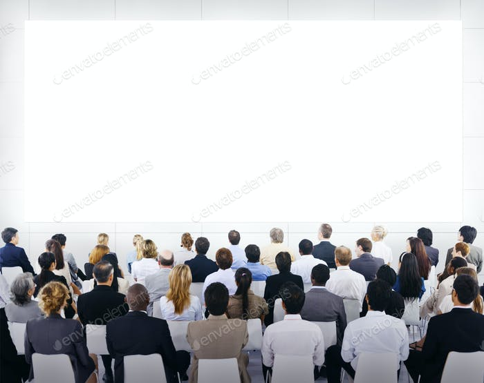 Group Of Business People Sitting And Looking At The Blank Presen