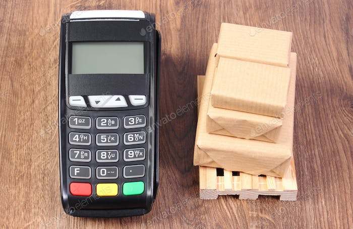 Payment terminal and wrapped boxes on wooden pallet, concept of paying for products and shipping