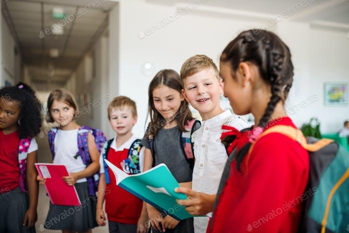 Eine Gruppe von fröhlichen kleinen Schulkindern mit Taschen im Flur, sprechen