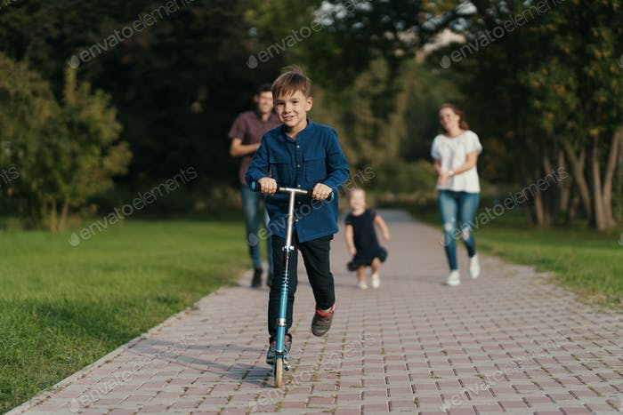 School boy riding a scooter in the park