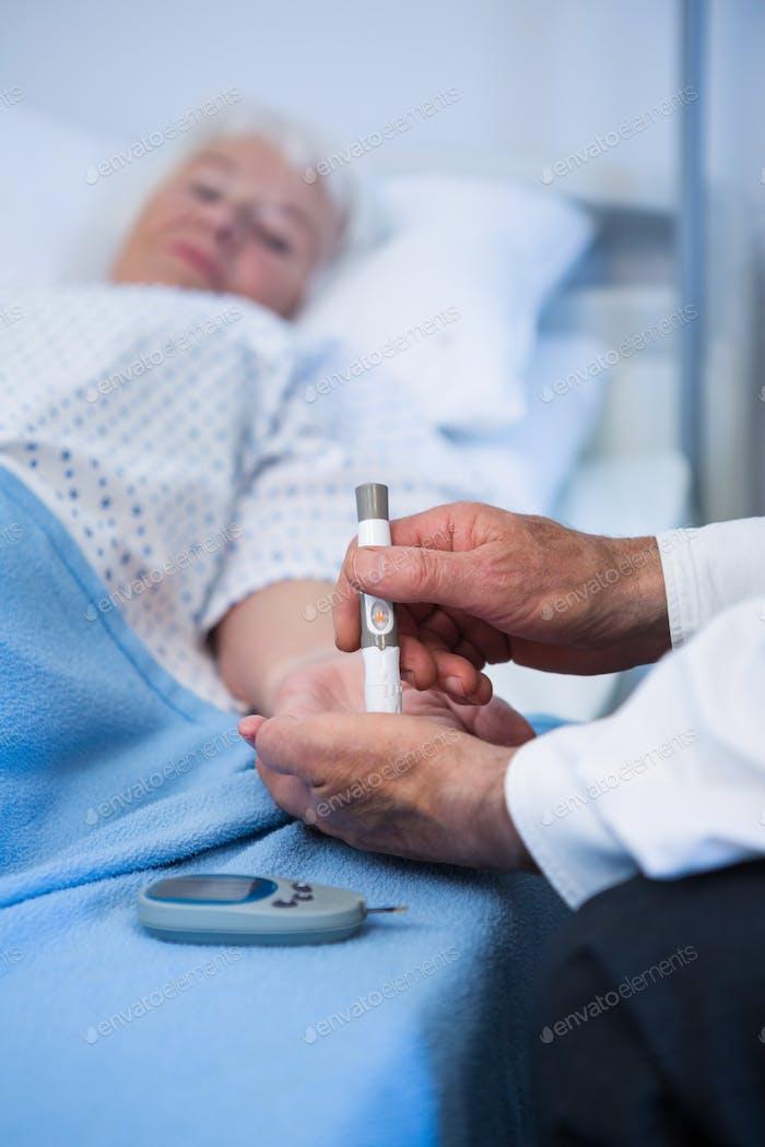 Doctor testing diabetes of senior patient with insulin pen