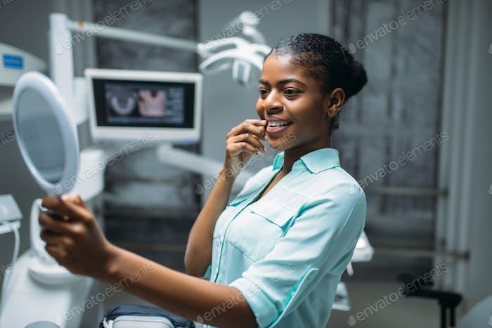 Patient looks on teeth in mirror, dental clinic