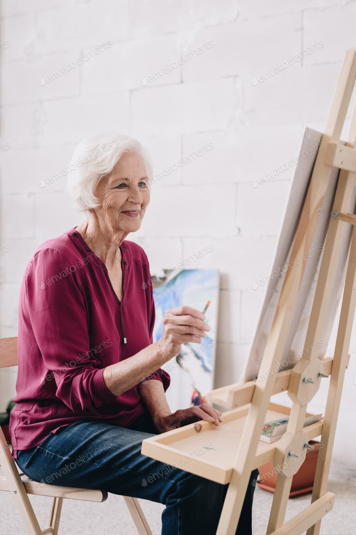 Smiling Senior Woman Painting at Easel
