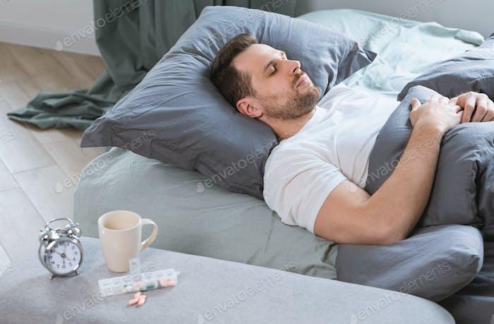 Man Sleeps In Bed After Taking Sleeping Pills In Bedroom