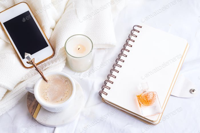 Phone, white cup of coffee and candle with notebook on white bed and plaid, cozy morning light