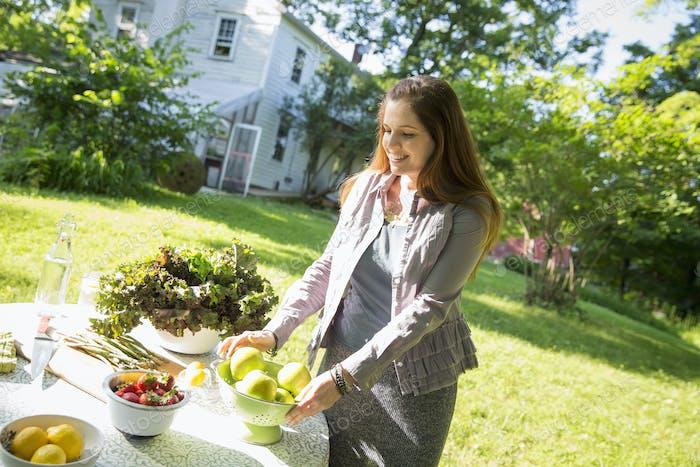 Una mujer en un jardín de granja, preparando alimentos frescos para una comida.