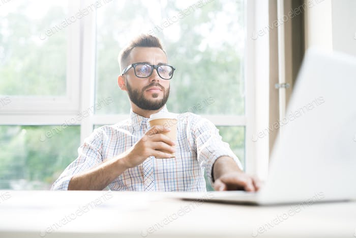 Successful Entrepreneur Drinking Coffee in Office