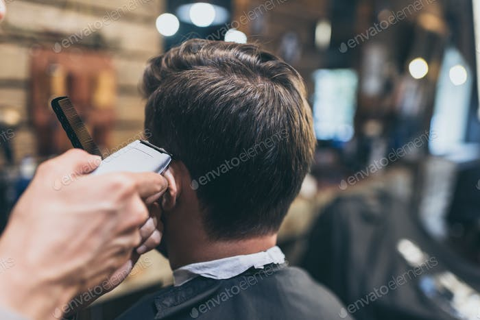 Male barber cutting hair of customer in barber shop