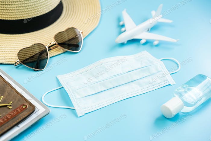 Sergical mask with travel items and passport, Travelling during corona virus epidemic concept