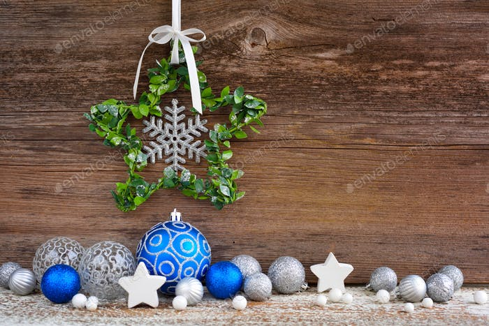 Christmas star with christmas balls on wooden background. Christmas or New Year greeting card.