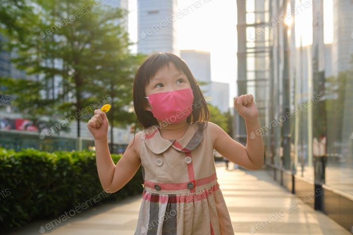 child in city street with mask