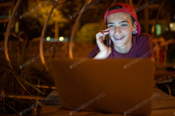 Portrait of a smiling young man with a smartphone, in the street at night.