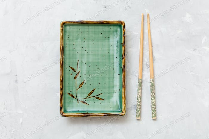 top view of green plate and chopsticks on concrete