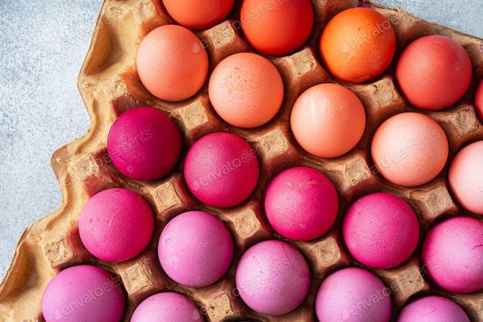 Varios huevos de Pascua en diferentes tonos de rosa en caja de huevos