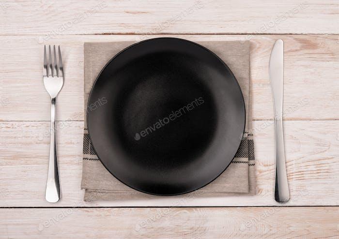 Draufsicht leerer schwarzer Teller, Besteck und Serviette