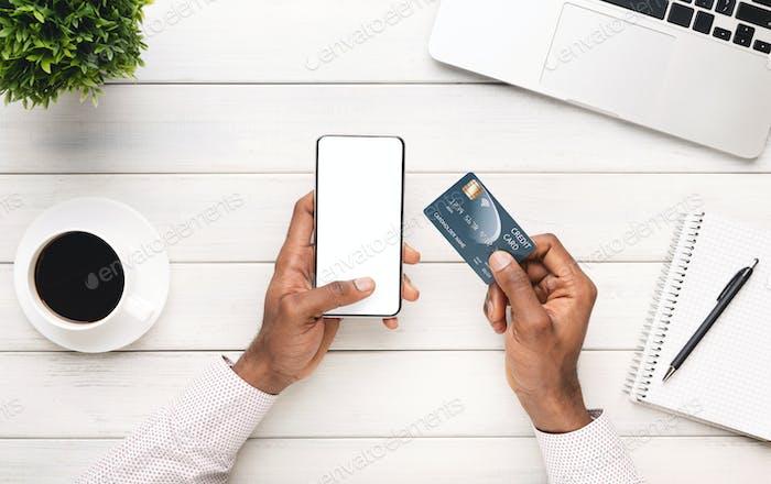 Schwarzer Mann hält Smartphone mit leerem Bildschirm und Kreditkarte