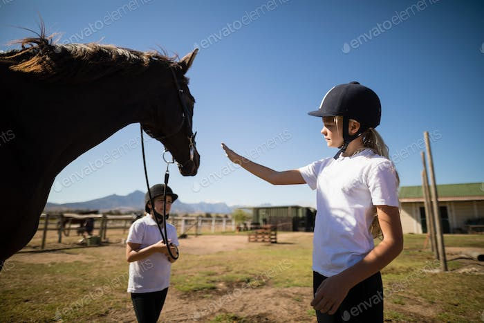 Two girls standing with a horse in the ranch