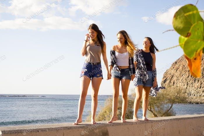 Group of three girls walking on a wall near the beach