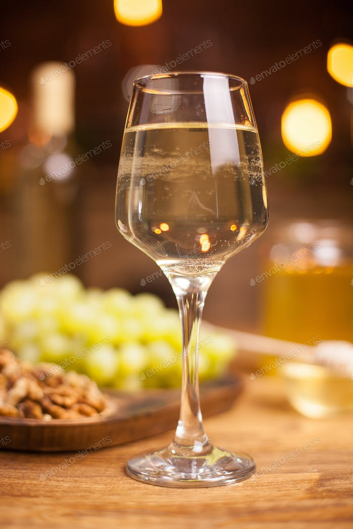 Close up photo of a glass of white wine on a wooden table