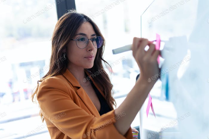 Business young woman working on white board with post it stickers in the office.