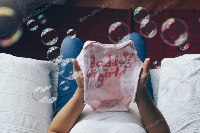 Pregnant woman holding baby clothes in her hands, top view