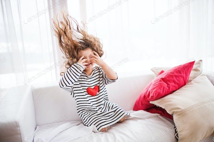 Ein kleines glückliches Mädchen in gestreiftem T-Shirt zu Hause Spaß.