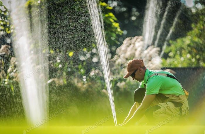 Worker Adjusting Water Sprinkler