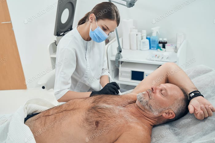 Man receiving underarm treatment in cosmetology clinic