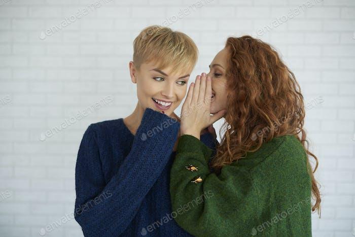 Mädchen flüstert ein Geheimnis zu ihrem Freund