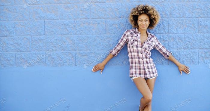 Mädchen stehend an der blauen Ziegelmauer
