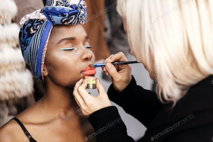 Professional make-up artist doing beautiful girl makeup in studio