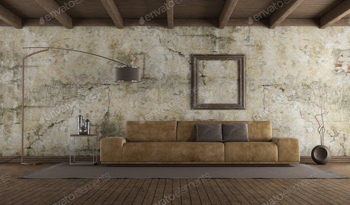 Современный кожаный диван в комнате со старой стеной