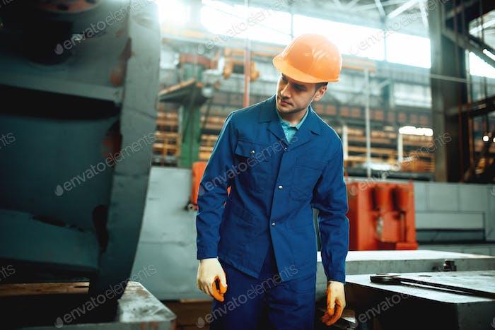 Arbeiter in Uniform und Helm, Metallverarbeitende Fabrik